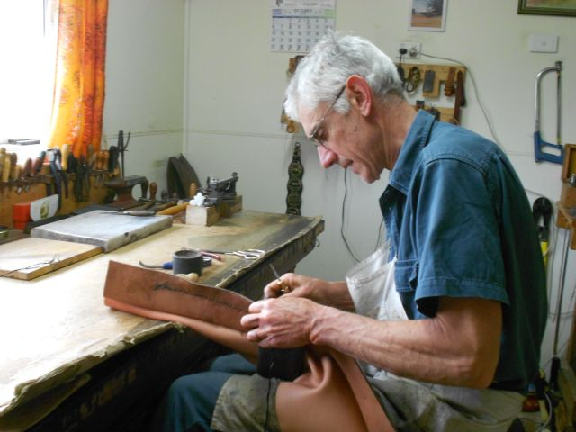 Mark Porter hand-sewing, with black-waxed thread, at his work-bench in Currawarna